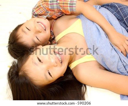 2 asian siblings lying in a bed smiling