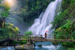 Asian woman tourist  stands on a bamboo bridge watching Pha Dok Siew Waterfall at Doi Inthanon National Park, Chiang Mai Province, Thailand.
