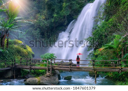 Asian woman tourist  stands on a bamboo bridge watching Pha Dok Siew Waterfall at Doi Inthanon National Park, Chiang Mai Province, Thailand. Stock fotó ©