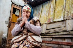 Ask for help. Poverty and misery. Slums. Poor areas. Seniors concept. The old grandmother bowed her head in prayer.The old grandmother on the background of the slums. Grandma is praying.