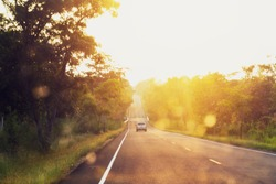 asphalt road at sunset with blur car