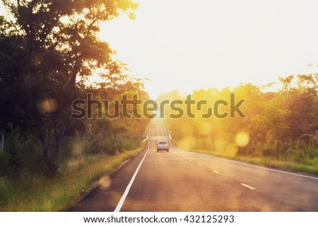 asphalt road at sunset with blur car