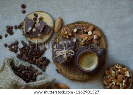 Assortment of different nuts with chocolate on a burlap background. A cup of delicious aromatic coffee on a wooden stand with grains. #1162901527