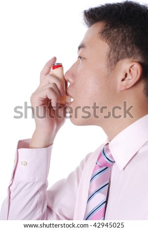 Asthma inhaler being used by Asian man