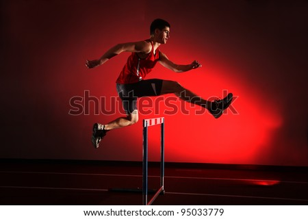 athlete running hurdles isolated on red background - stock photo