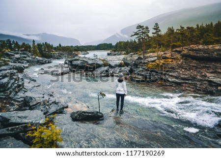 Attractive blond girl Young Woman hiker enjoys nature in Norway during a rain day