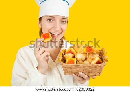 Attractive cook girl in toque with pastry over yellow background