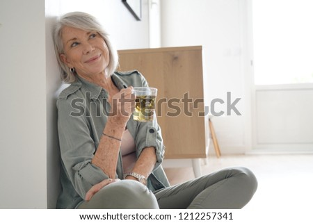 Attractive senior woman sitting on the floor at home                               #1212257341