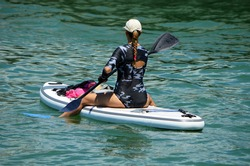 attractive young bond woman paddling a paddle board from a seated position