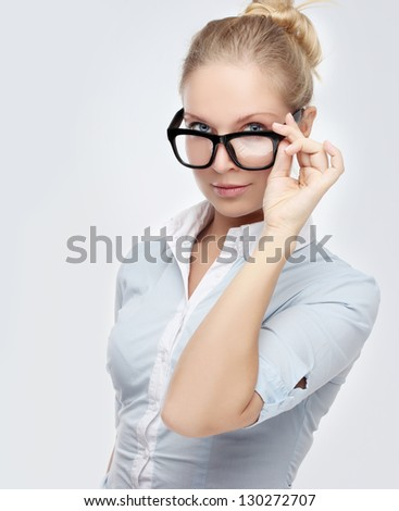 Attractive young woman pulls down here eye glasses  while pouting at the camera.