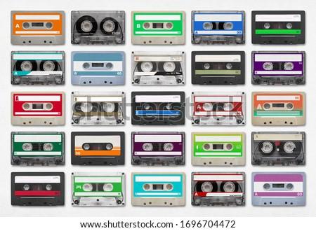 Photo of  25 audio cassettes isolated on white background.