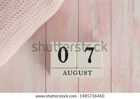 7 August Date on Cubes. Date on painted pink wood, next to baby blanket. Theme of baby due dates and birth dates. #1485736460