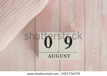 9 August Date on Cubes. Date on painted pink wood, next to baby blanket. Theme of baby due dates and birth dates. #1485736478