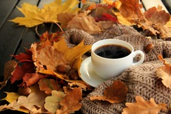 Autumn, fall leaves, hot steaming cup of coffee and a warm scarf on wooden table background. Seasonal, morning coffee, Sunday relaxing and still life concept.