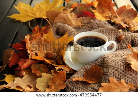 Autumn leaves, hot steaming cup of coffee and a warm scarf on wooden table background. Seasonal, morning coffee, sunday relax and still life concept