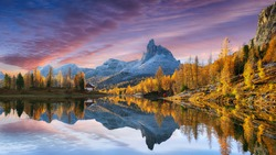autumn view of  Lake Federa in Dolomites  at sunset. Fantastic autumn scene with colour sky, majestic rocky mount and colorful trees glowing sunlight in Dolomites. Location: Federa lake with Dolomite