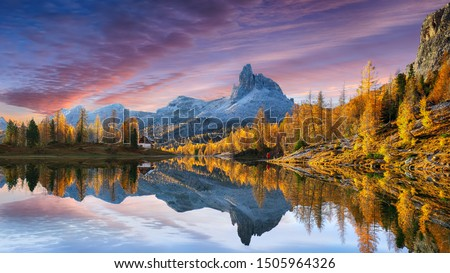 Photo of   autumn view of  Lake Federa in Dolomites  at sunset. Fantastic autumn scene with colour sky, majestic rocky mount and colorful trees glowing sunlight in Dolomites. Location: Federa lake with Dolomite
