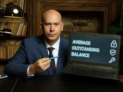 AVERAGE OUTSTANDING BALANCE inscription on the screen. Close up Bookkeeping clerk hands holding black smart phone.