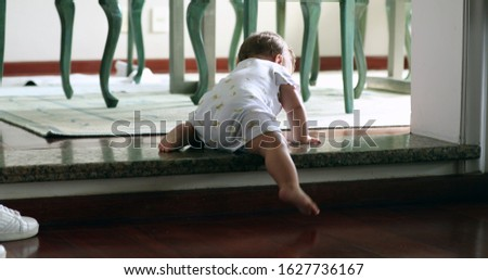 Baby climbing down step for first time. Toddler infant learning to climb down stair by himself, effortful infant development
