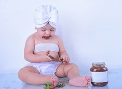 baby dressed in white with turban on her head, eating chocolate cream with strawberries
