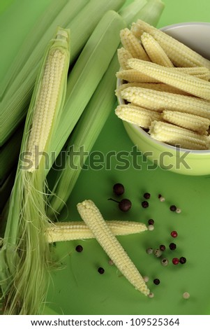 Baby sweetcorn cobs/ baby corn cobs  isolated on green background / top view