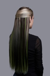 Back shot of lady with black and green tresses in her long blonde hair. Girl in black blouse is posing on the gray background.