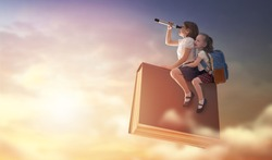 Back to school! Happy cute industrious children are flying on the book on background of sunset sky. Concept of education and reading. The development of the imagination.