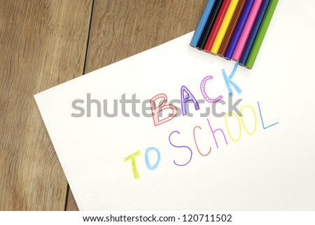 """Back to school"" sign  on the white paper on the wooden table"