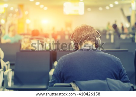 Back view of Business man while listening to music.young man in headphones working on laptop while sitting at airport,Businessman Relaxing Listening To Music,selective focus ,vintage color