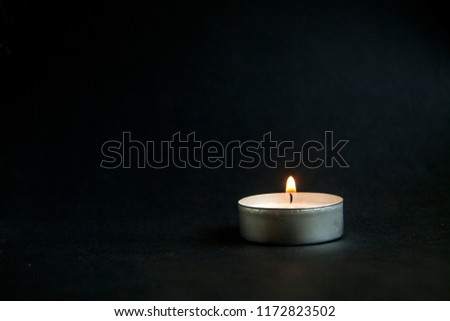 background of sorrows lonely candle on a dark black texture