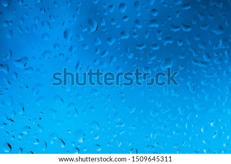 Background of water droplets in blue glass