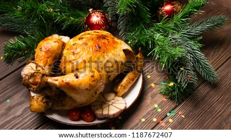 Baked turkey chicken served on a plate stands on a table with a festive serving. New Year's Christmas concept. Vertical shot. Copy space. #1187672407