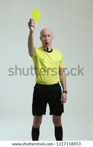 bald football referee on white background.  the referee shows a yellow card and looks into the frame. soccer referee in yellow uniform on white background. referee raised a yellow card and whistles.