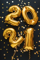 2021 balloon gold text on black background with golden confetti, festive decor. Happy New year eve invitation with Christmas gold foil balloons 2021. Vertical