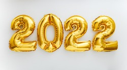 2022 balloon text on white background. Happy New year eve invitation with Christmas gold foil balloons 2022. Flat lay long web banner