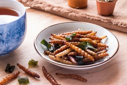 Bamboo worm edible insect crispy mixed with pandan, Thai pepper powder in a plate with tea on wooden table background. Fried insects are popular snack food in Thailand, Close-up, Horizontal image