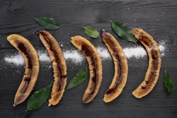 Banana dessert with mint on a black background. Traditional Thai and Asian restaurant menu recipe, Horizontal photography with black background. Top view, flat, overhead.