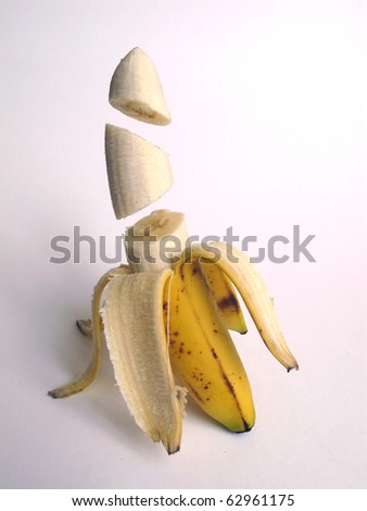 banana sliced and with floating pieces on white background