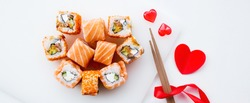 Banner. Valentine's Day. Sushi and sticks on a white background. The concept of a romantic dinner at a sushi bar. The portfolio has more images by February 14th.