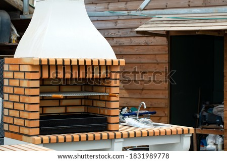 Barbecue open fireplace for cookout food. Outdoor BBQ Grill. Open Summer Kitchen. Barbeque Grill Made From Bricks On The Backyard Stock photo ©