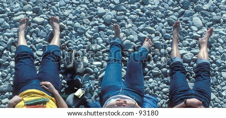 3 barefooted girls sunbathing on a stone covered beach.