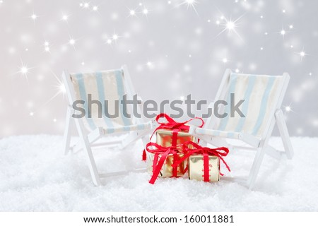 beach chair  and christmas gifts in snow before twinkled background