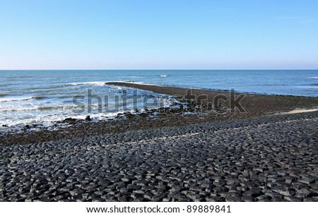 Beach in Holland by the North Sea with black boulders and breakwater.
