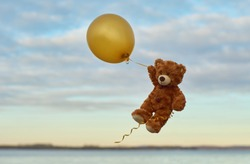 Bear Teddy flies through the sky in a yellow balloon.  Bear with yellow balloon. Toy in the sky. Pooh and balloon. Winnie the Pooh.
