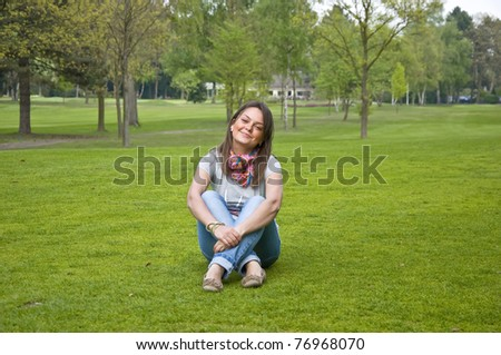 Beautiful attractive woman sitting on a green grass golf course. Smiles.