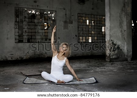 Beautiful blond woman exercises in an abandoned house