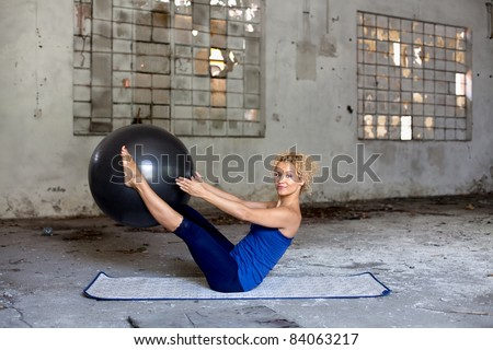 Beautiful blond woman exercises with a fitness ball in an abandoned house