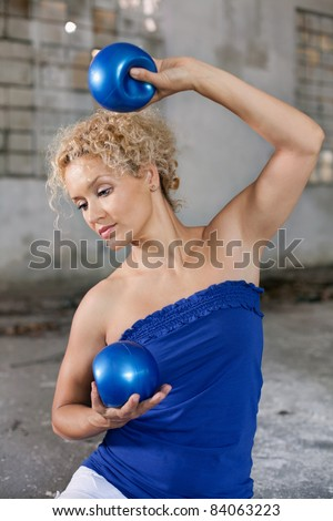 Beautiful blond woman exercises with a fitness balls in an abandoned house