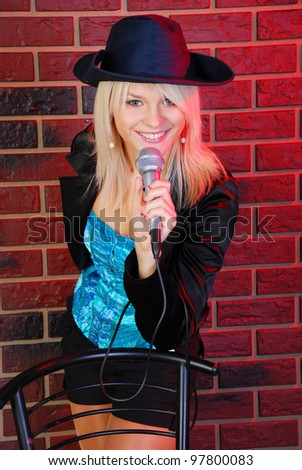 beautiful blond young woman portrait with microphone , studio shot