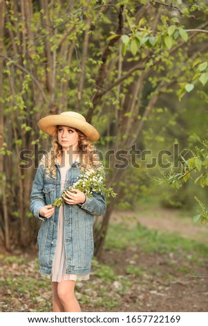 beautiful blonde girl with a bouquet of flowering branches in a straw hat and in a blue jeans jacket in a spring garden where trees bloom